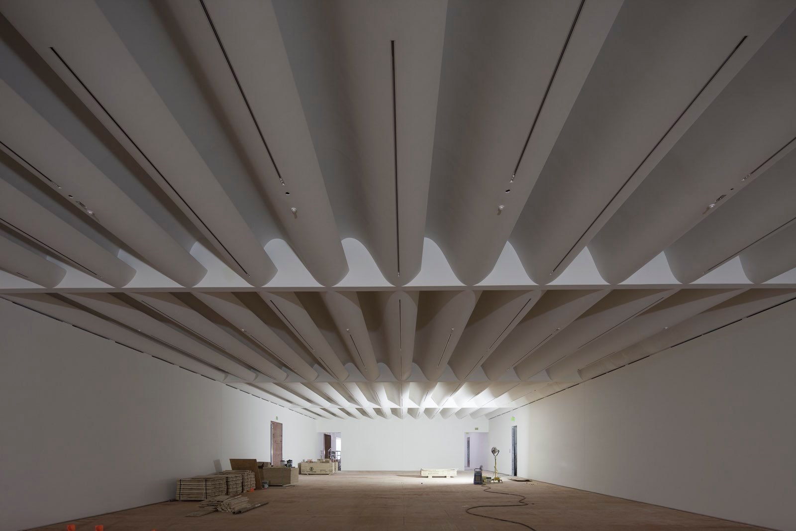 A cavernous room with an undulating white ceiling