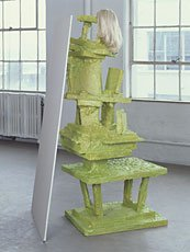 green sculpture with blonde wig in front of windows
