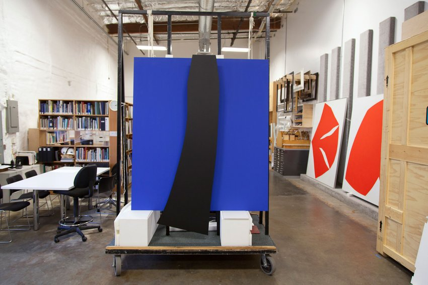 A large blue painting with a black stripe down the middle is loaded onto a palette for transport in an art storage facility