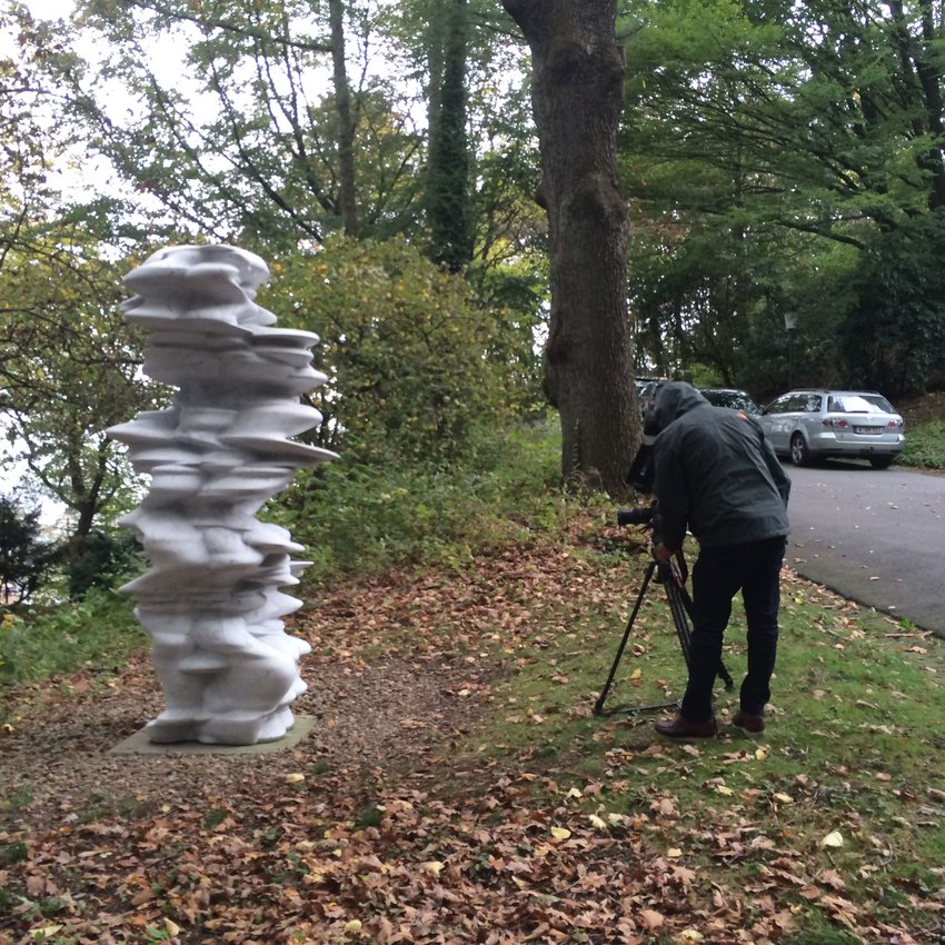 A hooded cameraman leaning over a tripod shooting a silver sculpture