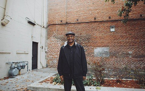 A portrait of an African American man in front of a brick wall