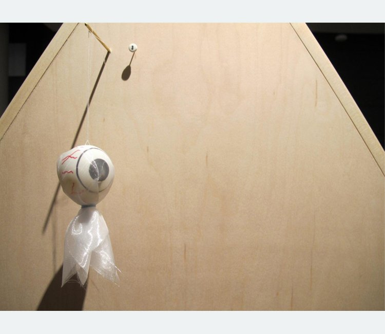 Plastic eyeball wrapped in translucent white fabric hanging off a dowel on a wooden board