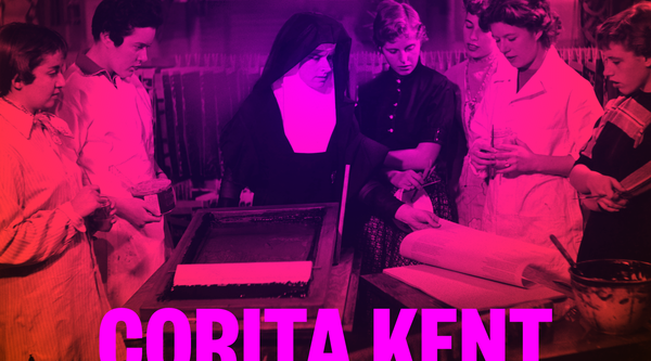 A fuschia toned black and white photograph of a nun in a habit at a screenprinting table surrounded by a group of young women