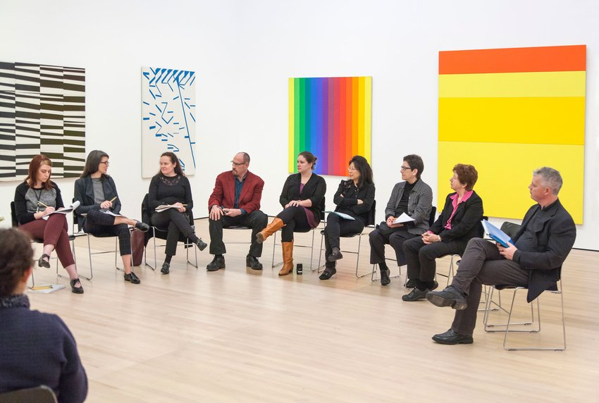 A group of people sitting in chairs arranged in a circle in a white gallery filled with colorful paintings