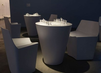 Two modern white tables, each with two empty white chairs. On each table are two all-white sets of chess pieces set up to start a match