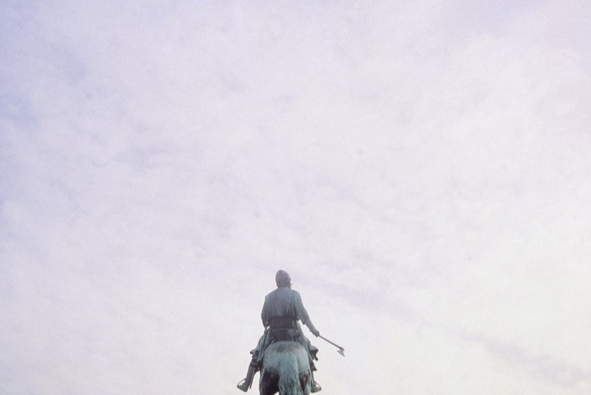 A statue of a man on a horse, seen against the sky