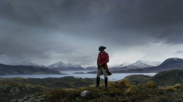 Man in red jacket and hat standing on grassy mountains in front of sea
