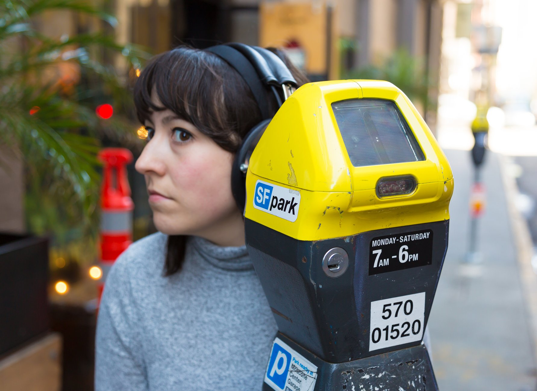 A Caucasian woman with brown hair appears to be listening to a parking meter, Kubisch Soundtracks