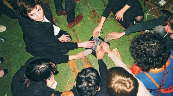 A group of people sit in a circle with their hands together in the center