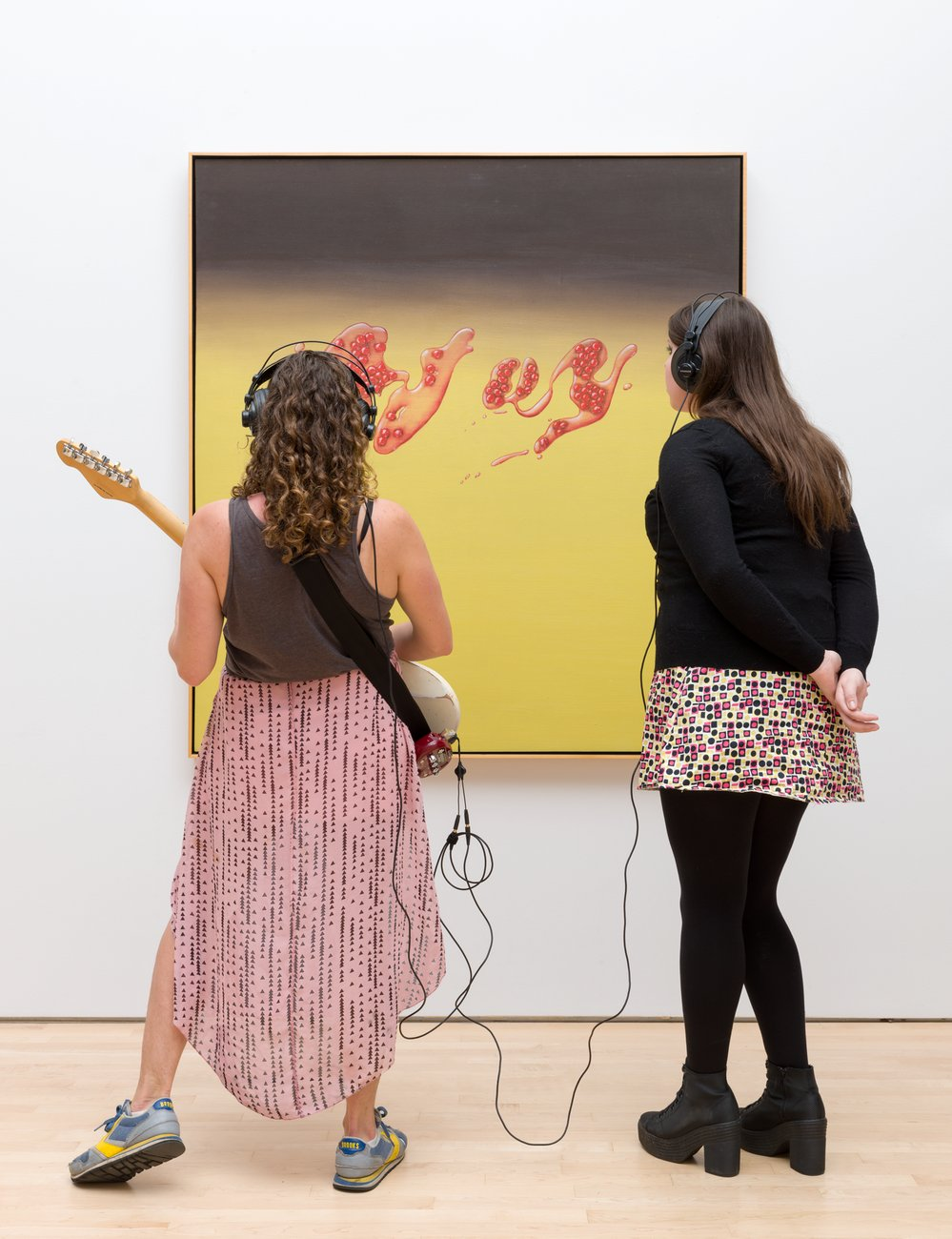 Two women, one playing a guitar and one wearing headphones, look at a painting, Kallmyer Allen, Soundtracks