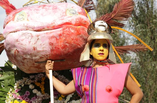 A woman with yellow facepaint, a gold helmet and a futuristic suit made of indigenous woven textiles holds a giant papier-machie axolotl head outdoors