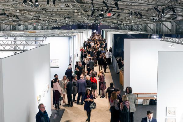 A crowded aisle at an art fair in a warehouse