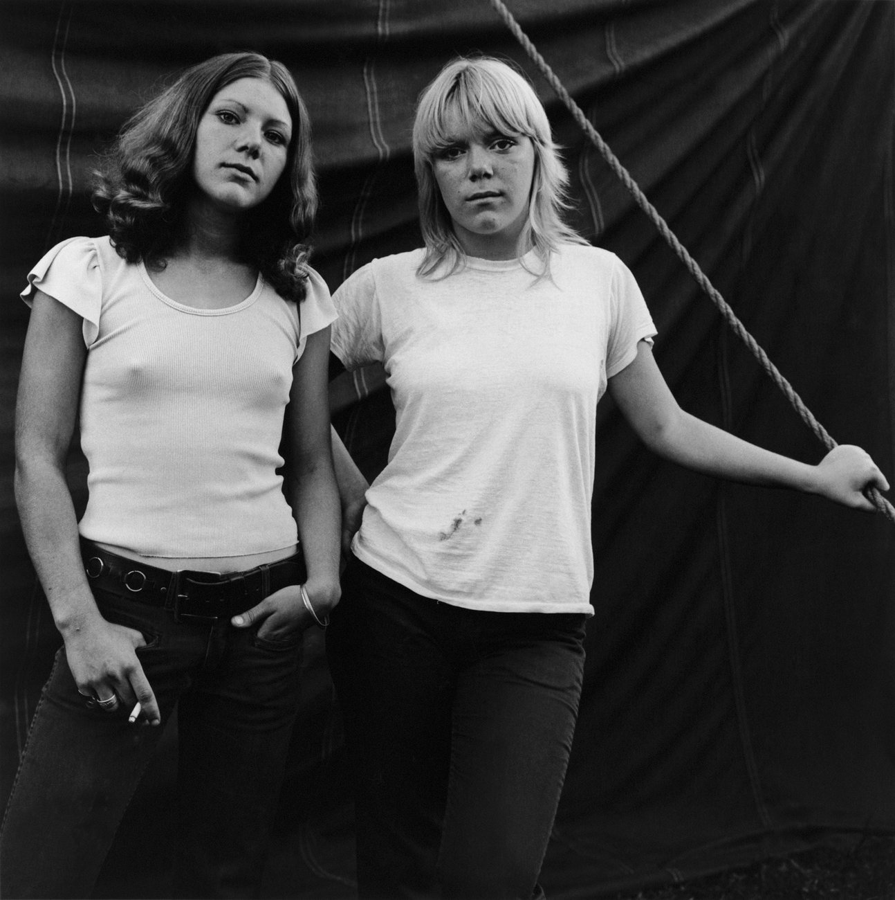 Black and white photo of two young women in tank tops and jeans standing in front of a curtain or tent