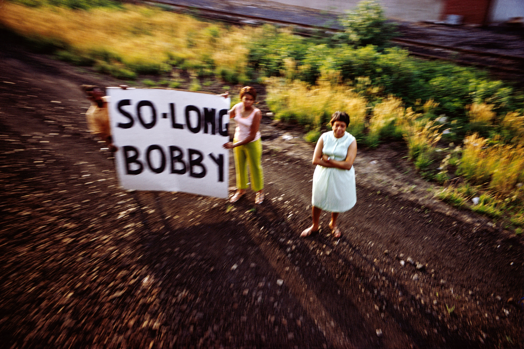 "Three blurry figures look up toward the camer, two hold a banner that reads, ""So-long Bobby"""
