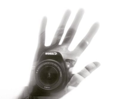 A camera emerges from the shape of a hand on a white screen