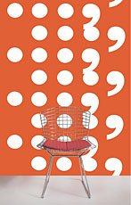 chair in front of orange wall covered in white circles and comma shapes