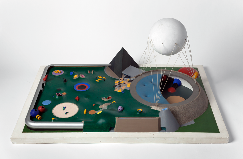 Table top model of a brightly colored pavilion with a large sphere suspended above, set into a lawn