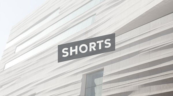 A rippling white building facade with the word SHORTS in white on a grey slice; SFMOMA Shorts