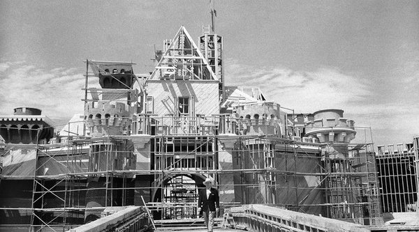 Walt Disney in front of a disnley land castle during construction
