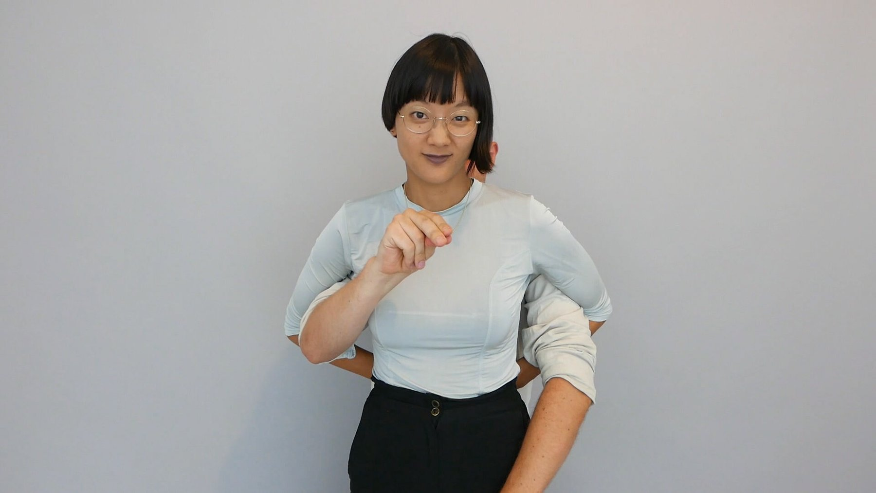 An Asian woman wearing glasses stands in front of a grey background with someone else's arms around her waist, Kim Soundtracks