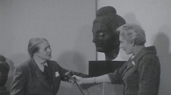Video still of Grace McCann Morley speaking in front of a sculpture
