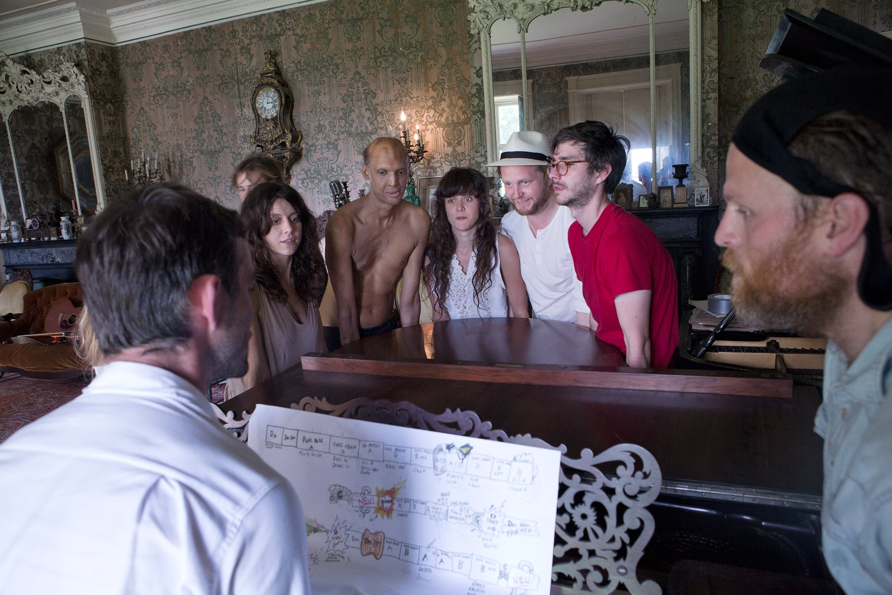 Several people stand around a piano in an elaborately decorated room, Kjartansson