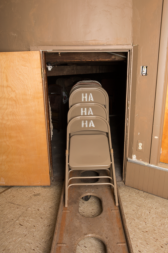 "Three stacking chairs with the words ""HA, HA, HA"" stenciled on the back"