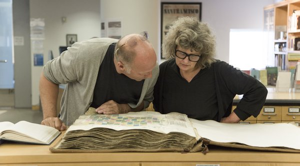 A middle-aged Caucasian man and woman look over an antique manuscript, Public Knowledge