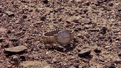 gold watch on dry rocky ground