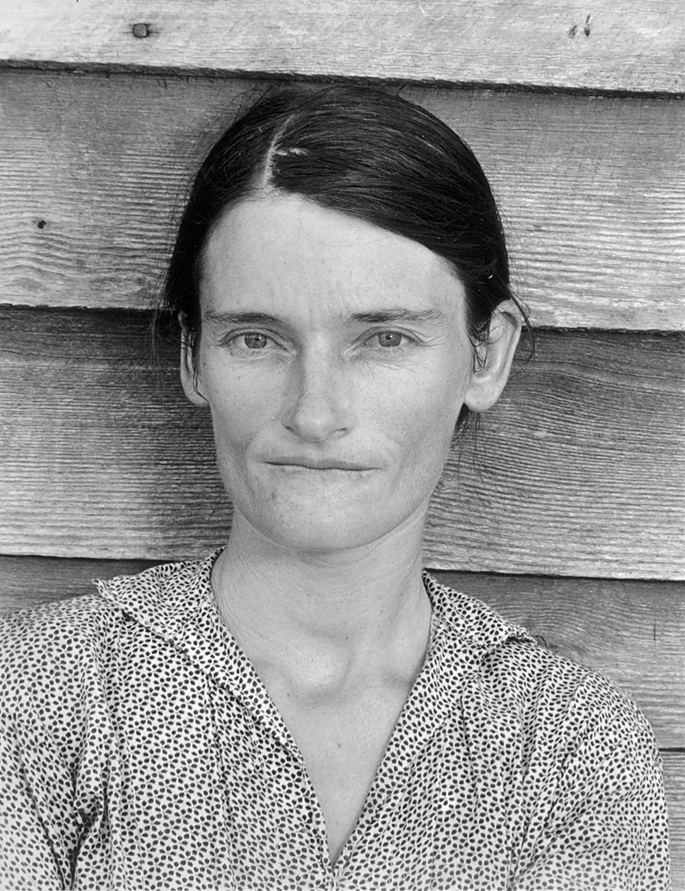 Portrait of a woman with a furrowed brow standing in front of an unpainted wood wall
