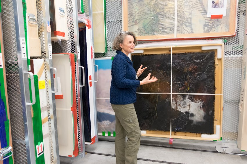 A woman stands before a black encaustic painting hanging on a storage wall
