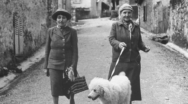 two women walking down the street with a poodle