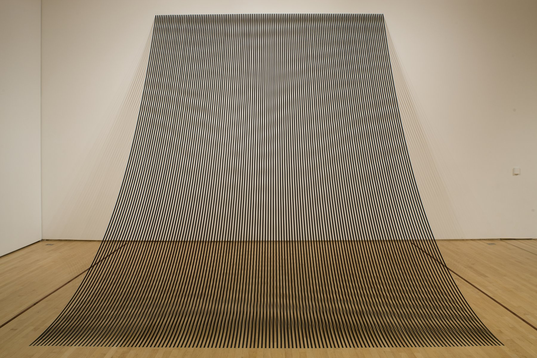 A sculpture made up of black strips that drape from the wall onto the floor