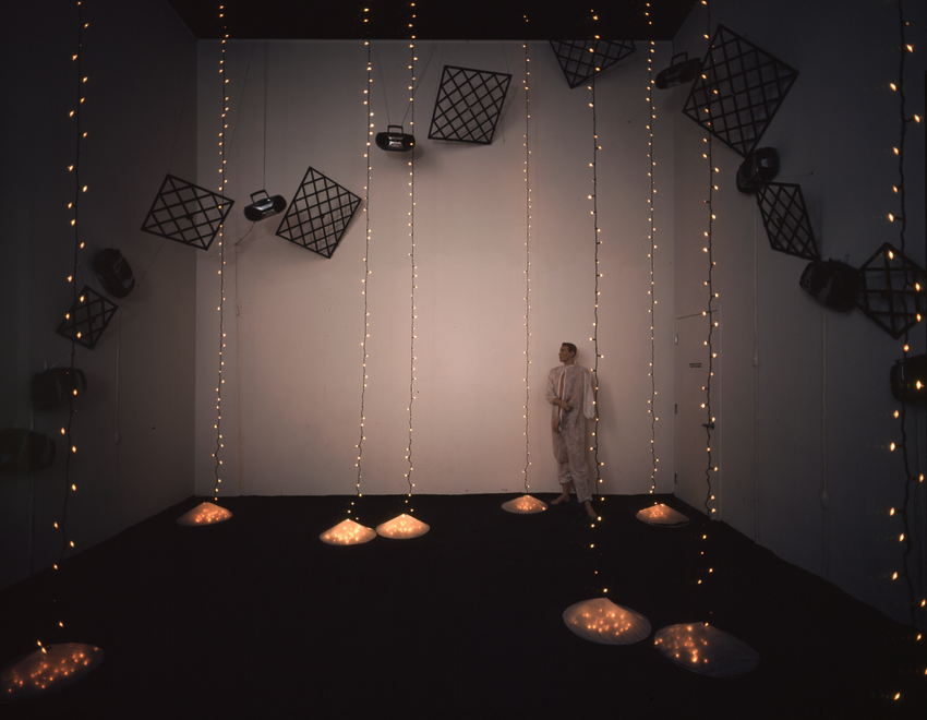A man in a tan suit stands in a dark room with hanging string lights, Eno Soundtracks