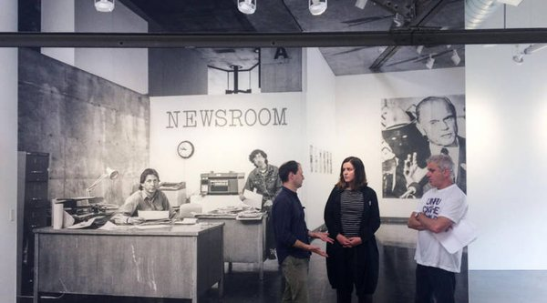 "A group of people stand in front of a wall with the words ""newsroom"" printed on the wall"