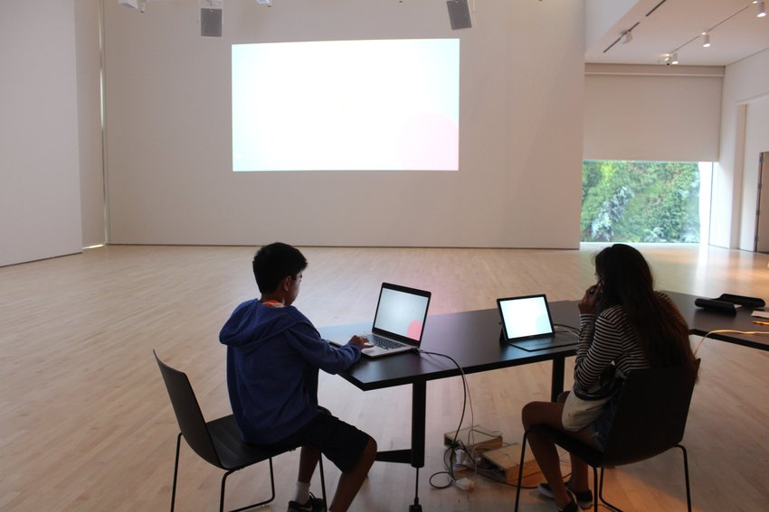 Two kids sit at a table with laptops playing a game whose image is projected on the wall
