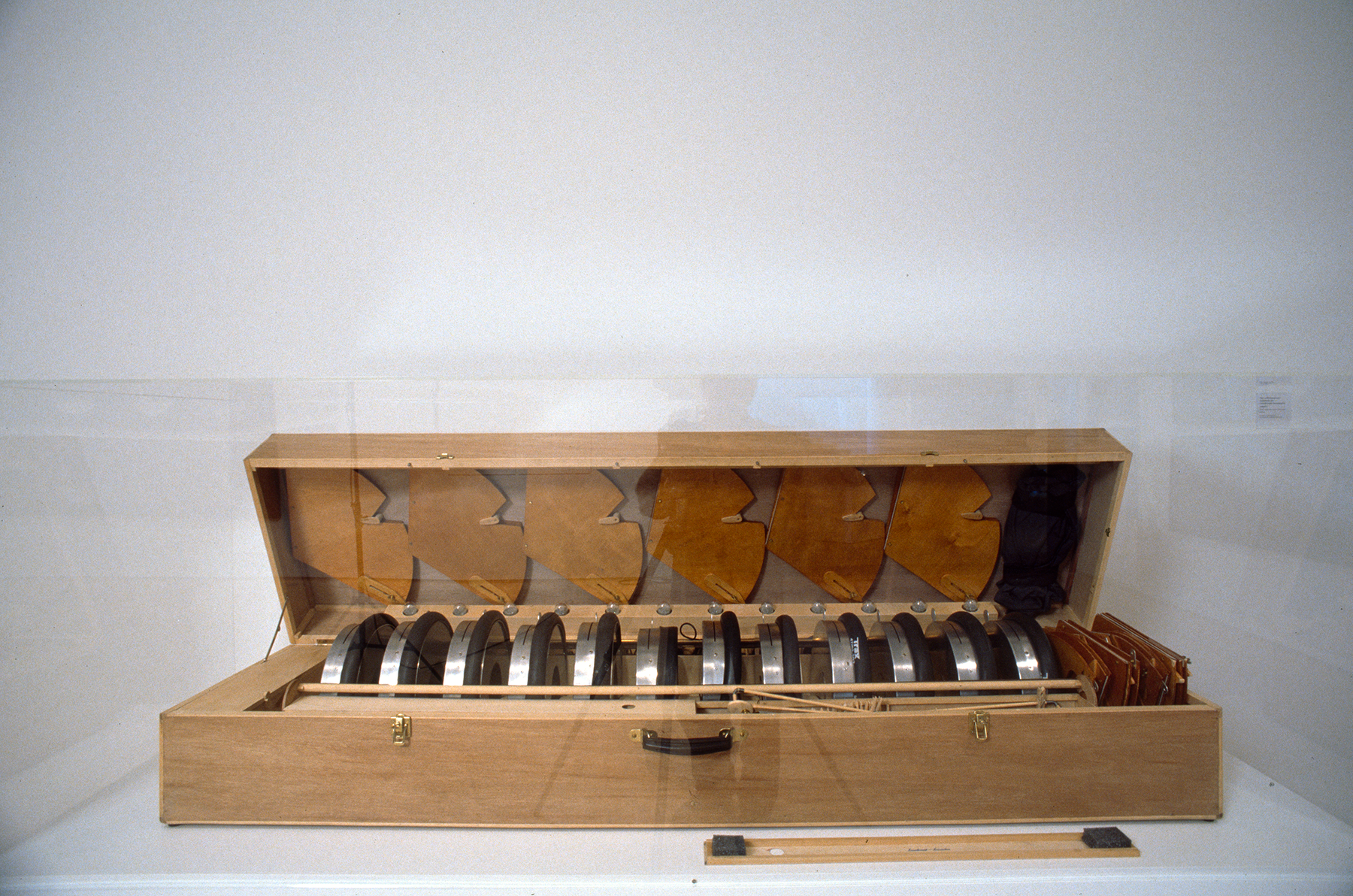 A large wooden case filled with metal and wooden objects