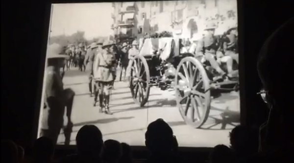 An audience watches a film screen showing a black and white image of a wagon, Limited Edition, Tawil
