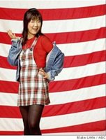 An Asian-American woman standing before an American flag
