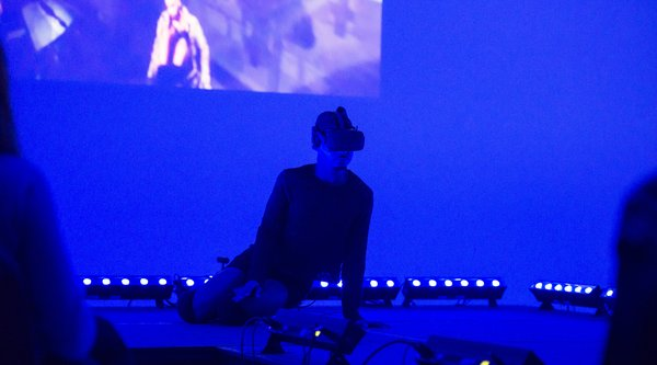 A man wearing a VR headset sits on a stage bathed in blue light with a video projection behind him as audience members look on