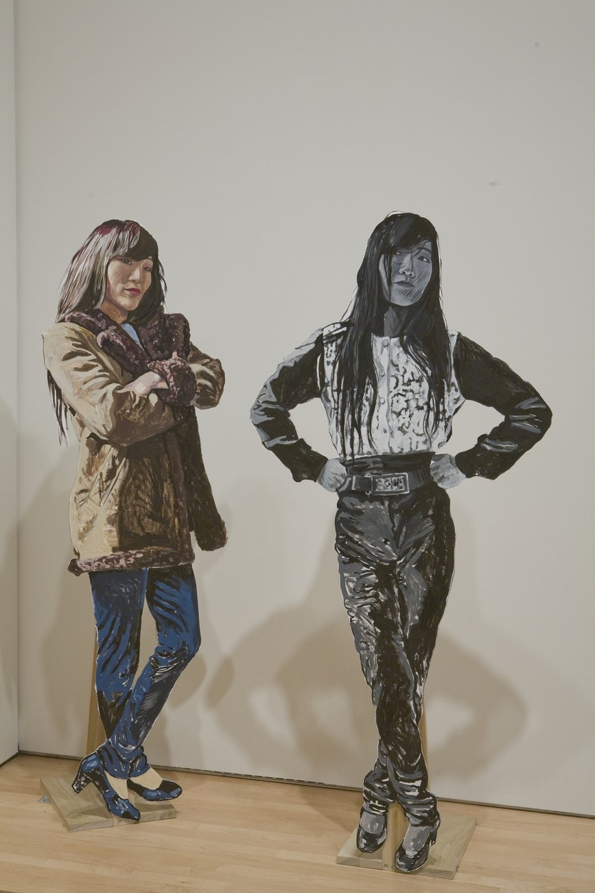 Two life-size cut outs of a woman in different poses