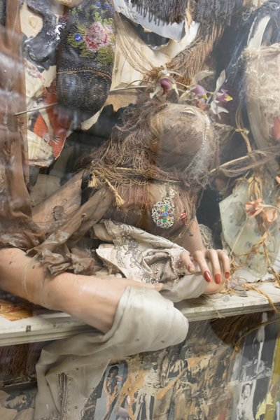 An assemblage artwork featuring mannequin hands, jewels, and fabrics