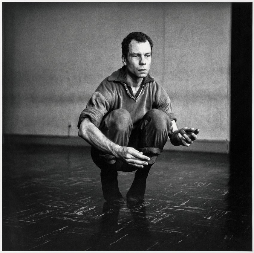 Black and white photograph of a Caucasian man squatting, Rauschenberg