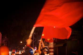 Dinh W. L, video still of crowd waving Vietnamese flag