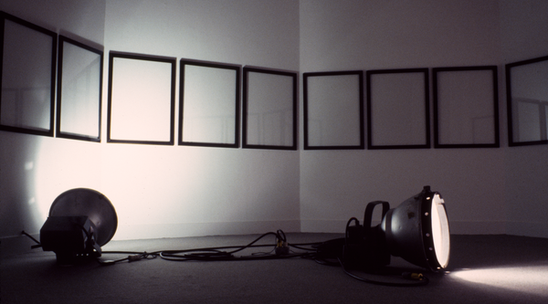 Two lamps in the foreground with a row of white canvases with black frames in the background