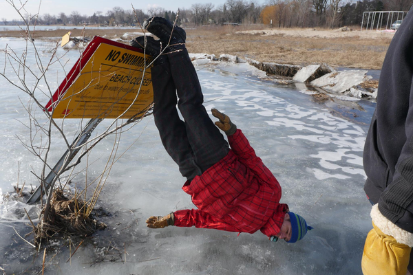 "A man leaning upside down on a ""no swimming"" sign on a frozen lake"