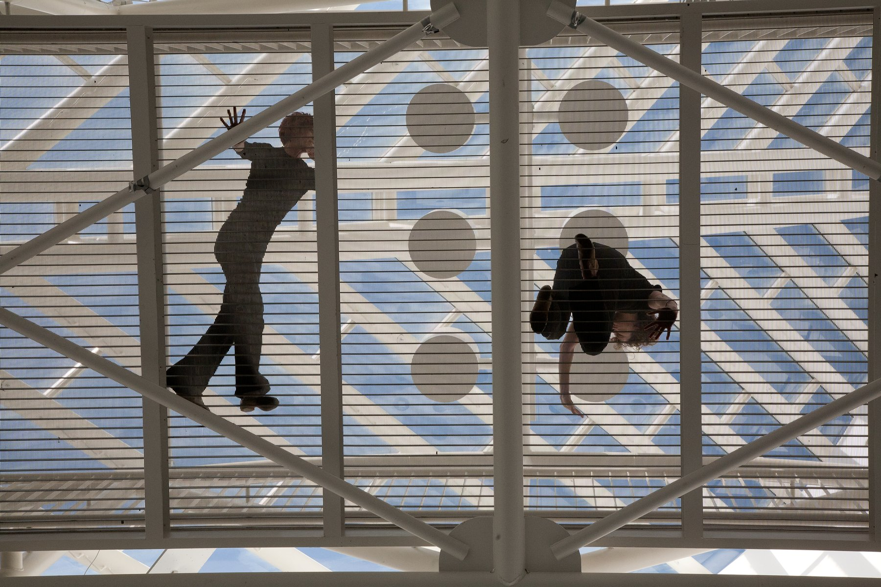 A white slatted bridge seen from below with dancers silhouetted