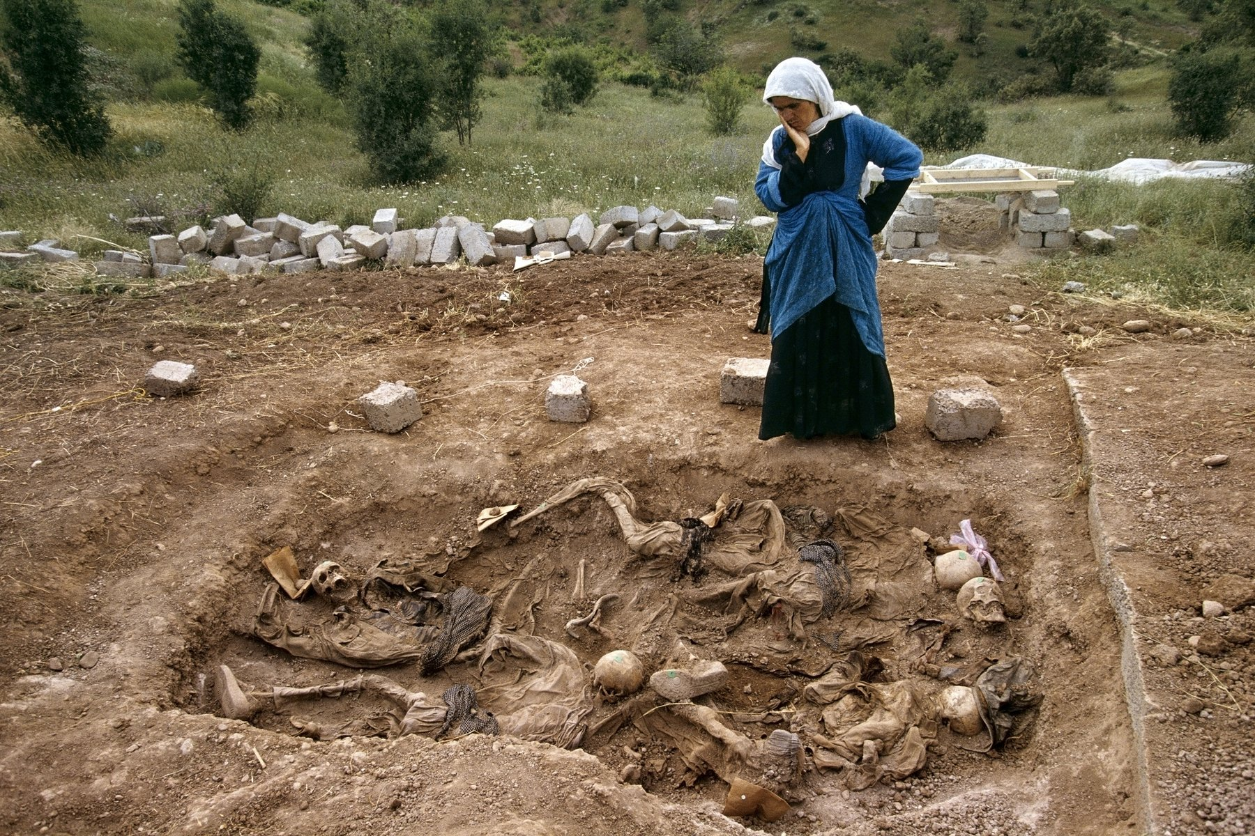 A woman touches her face as she looks down into a mass grave