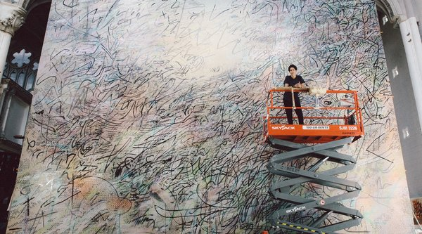 An African American woman stands on a lift in front of a massive abstract canvas, Julie Mehretu