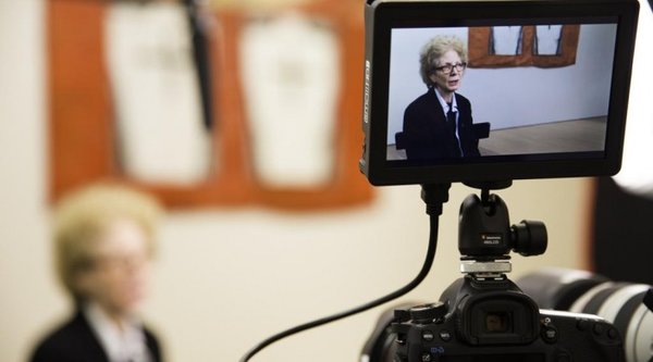 Woman being interviewed as seen through the screen viewer of a digital video camera